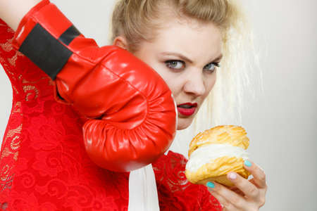 Woman fighting with her bad habits, being on diet. Female wearing boxing glove holding sweet dessert, cream cupcake. Stockfoto