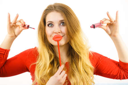 Young adult woman applying lipstick or lip gloss, getting her make up done holding fake lips on stick Stock Photo
