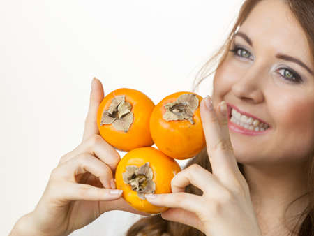 Woman holding persimmon kaki fruits in hands. Healthy eating, aid in weight loss, improve digestion.