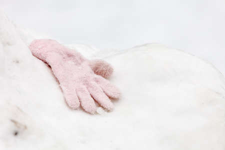 One old rotten warm glove on white snow during winter. Lost piece of clothing