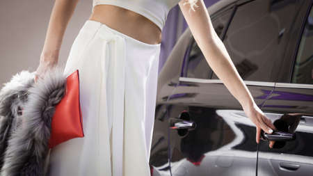 Glamurous female fashion model, elegant unrecognizable woman opening car holding handle to her exclusive auto