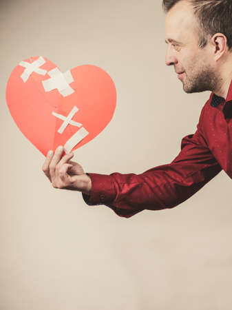 Bad relationships, breaking up, sadness emotions concept. Adult man holding broken heart, on grey Standard-Bild