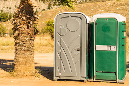 Capsule public toilet on sandy beach during summertime. Port a potty outdoor.