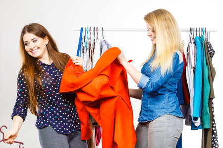 Happy young women shopping. Female friend helping in choosing perfect autumnal jacket.