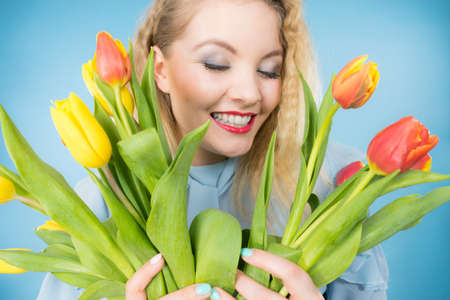International womens day, eight march. Beautiful portrait of pretty woman blonde hair with red yellow tulips, fashion make up. Mothers day. On blue Foto de archivo