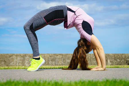 Super fit attractive young woman wearing fashionable outfit working out being active outside during sunny weather. Stretching her back or practice yoga