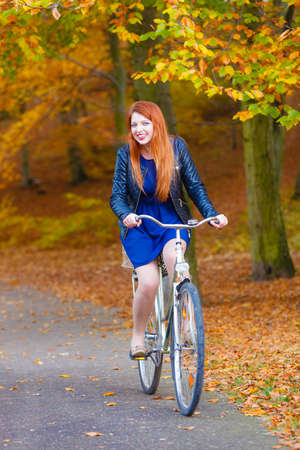 Woodland forest fall outdoor fitness concept. Girl in dress on bike. Young lady in elegant clothes in autumnal park with bicycle.