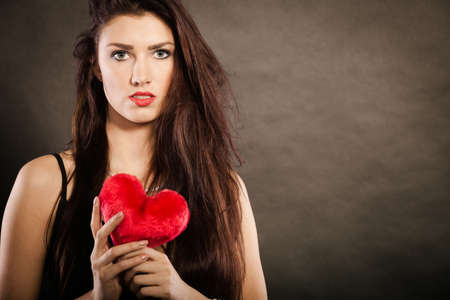 Woman brunette long hair girl wearing black sensual dress holding gift in form of red heart love symbol studio shot on dark. Valentines day happiness concept