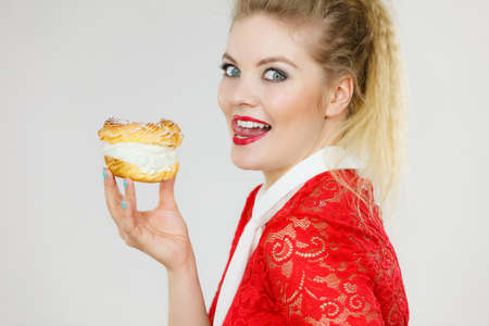 Sweet food and happiness concept. Funny joyful blonde woman holding yummy choux puff cake with whipped cream.