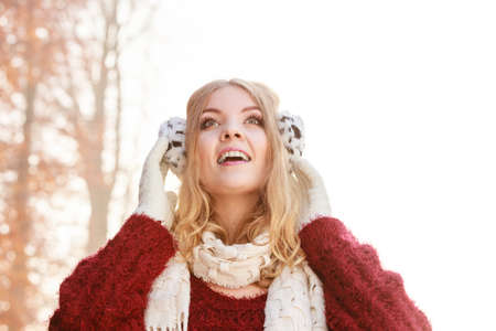 Portrait of pretty smiling fashionable woman in fall forest park. Happy gorgeous young girl in earmuffs and sweater pullover. Autumn winter fashion. Reklamní fotografie