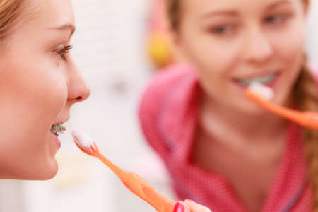 Woman brushing cleaning teeth. Girl with toothbrush in bathroom looking at mirror. Oral hygiene. Banque d'images