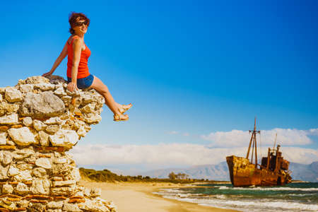Travel freedom. Mature tourist woman on beach enjoying summer vacation. An old abandoned shipwreck, wrecked boat in the background Stock Photo