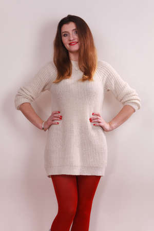 Portrait of young long hair female, woman wearing white sweater red warm pantyhose
