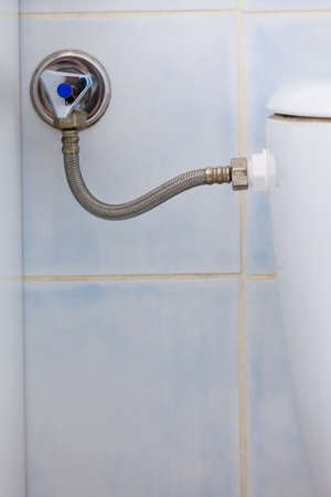 Bathroom and hydraulics objects concept. Toilet water supply wire with tap