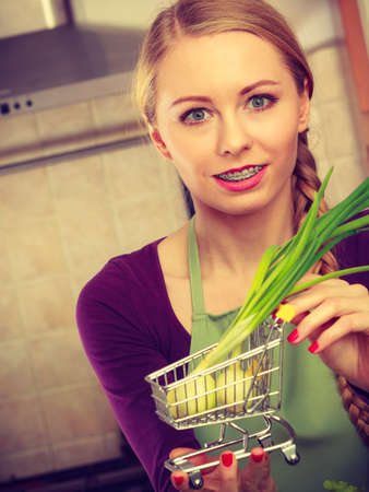 Buying healthy dieting food concept. Woman in kitchen having many green vegetables holding small shopping cart trolley with chive inside. Banco de Imagens - 107350855
