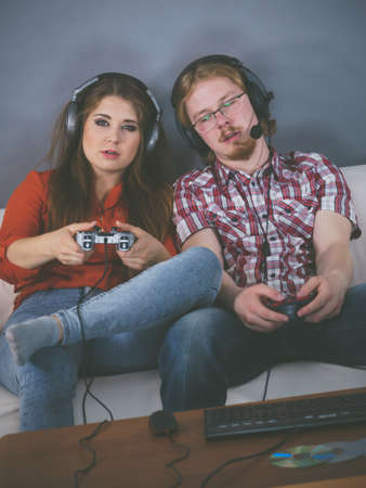 Happy couple enjoying leisure time by playing video games together. Studio shot 写真素材