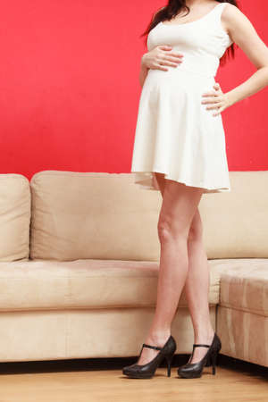 Maternity clothes, pregnancy concept. Pregnant woman standing in white dress wearing black high heels showing her belly on red background.