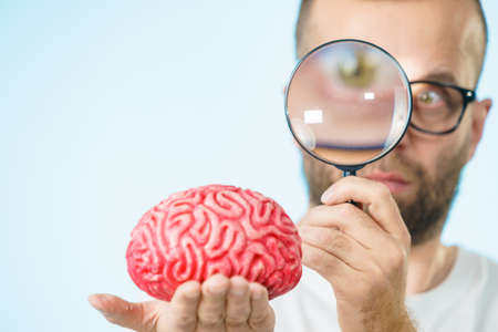 Adult nerd man wearing eyeglasses looking at human brain model. Thinking and intelligence conept