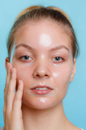 Young woman in facial peel off mask.