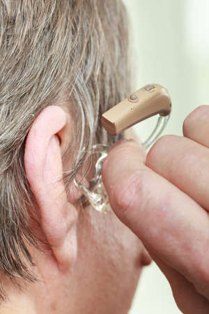 Closeup senior woman with hearing aid in her ear. Health care, hear amplify, device for the deaf. Reklamní fotografie