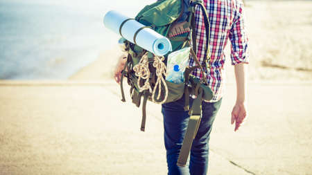 Man hiker backpacker walking with backpack on sea shore at sunny day. Adventure, summer, tourism active lifestyle. Young long haired guy tramping
