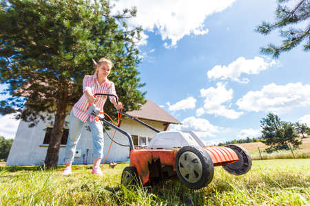 Gardening, taking care of house backyard, agricultural concept. Female person mowing green lawn with lawnmower in sunny day. Imagens