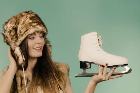 Girl wearing a warm hat and furry waistcoat holding and looking at ice skate