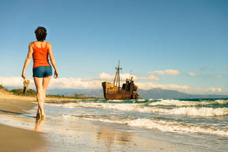 Travel freedom. Mature tourist woman walking on beach enjoying summer vacation. An old abandoned shipwreck, wrecked boat in the background