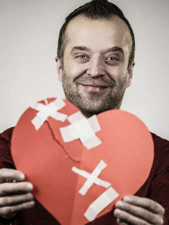 Healed love. Valentines Day concept. Adult smiling man holding big red heart with plaster. Male healing relationship. Stock fotó