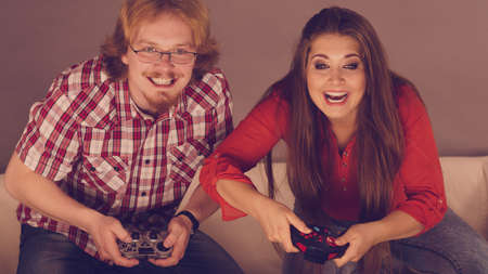 Happy couple enjoying leisure time by playing video games together. Studio shot Banco de Imagens