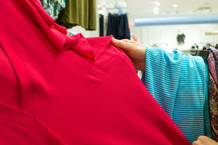 Unrecognizable person in shopping store. Human in clothes shop looking and choosing clothing.