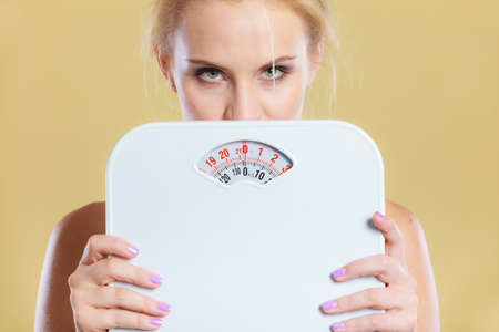 Frustrated sad blonde girl covering her face with scales. Weight gain, time for slimming weightloss, diet. Stock Photo