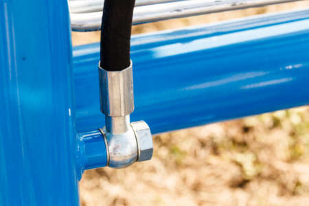 Industrial detailed pneumatic, hydraulic machinery concept. Pump made of steel on blue machine closeup. Stock Photo