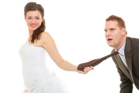 Concepto de comando de relación. Novia dominante con vestido de novia tirando de la corbata del novio, aislado.