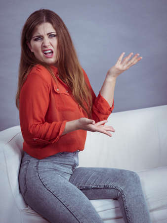 Angry, pissed off young woman. Attractive female with long brown hair sitting on sofa being mad and irritated having displeased face expression.