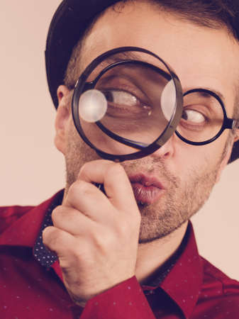 Funny adult guy wearing weird eyeglasses investigating something using magnifying glass making his eye looking big.
