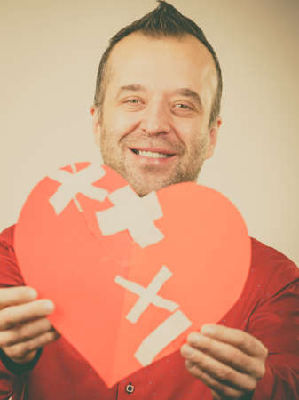 Healed love. Valentines Day concept. Adult smiling man holding big red heart with plaster. Male healing relationship. Stock fotó - 114679880