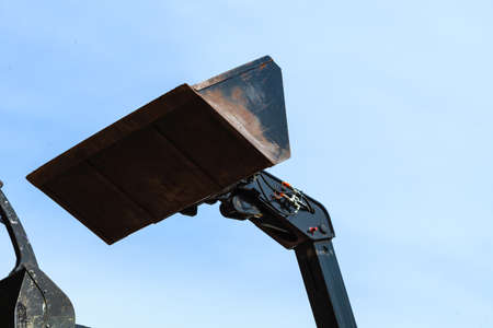 Machines, architecture building, heavy equipment concept. Bucket loader with blue sky in background