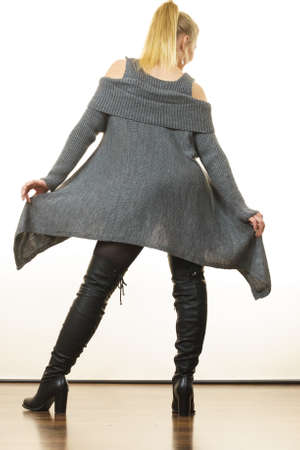 Woman in ponytail wearing gray long top sweater tunic, black tights. Stylish, autumnal outfit. 免版税图像
