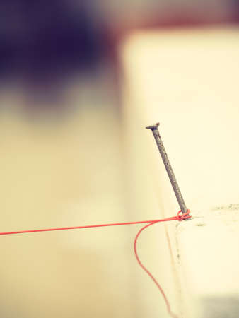Close up of string net placed on spike nail. Tool to help you set straight distances, spirit level. Stock Photo