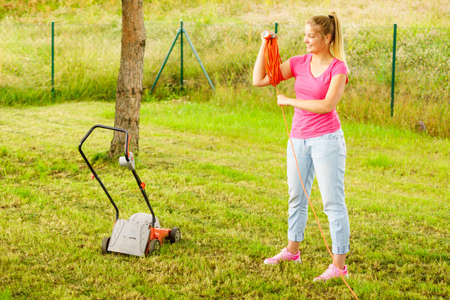 Young blonde woman holding work tool rolling up cable garden extension cord.