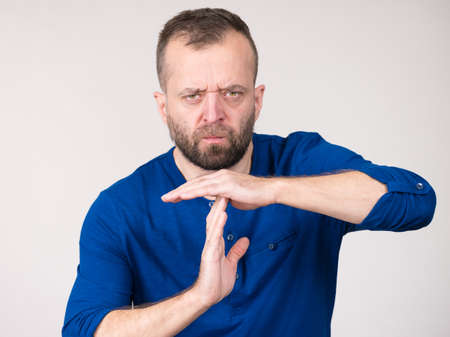 Adult angry rude man showing time stop gesture with his hands. Studio shot