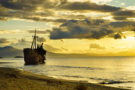 An old abandoned shipwreck, wrecked boat sunken ship stand on beach coast. Scenic sunset sky Stock Photo