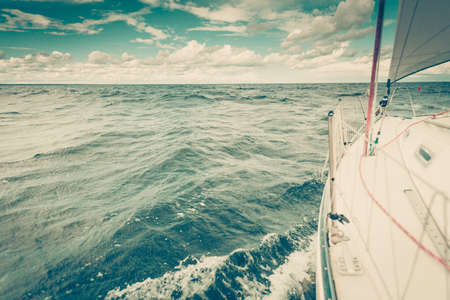 Yachting on sail boat bow stern shot splashing sea water. Sporty transportation conept. Reklamní fotografie