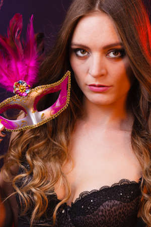 People celebration concept. Masquerade. Beautiful girl holding carnival mysterious mask on dark Stock Photo