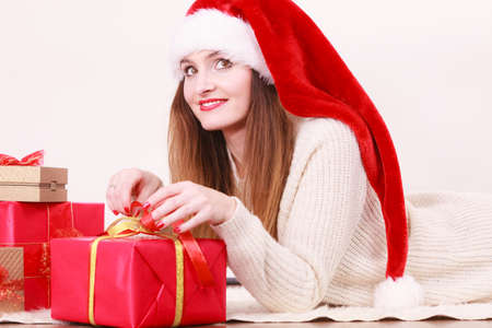 Christmas winter happiness concept. Woman wearing santa helper hat with many presents red golden gift boxes