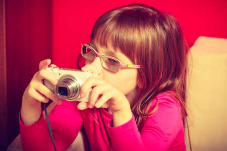 Childhood, childcare, discovering new hobbies and passion concept. Little toddler girl wearing eyeglasses sitting on sofa and playing with digital camera.