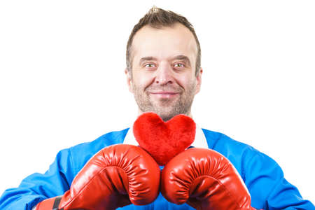 Guy ready to fight for love. Adult man wearing red boxing sporty gloves holding heart shape. Winning with cardiology disease concept.