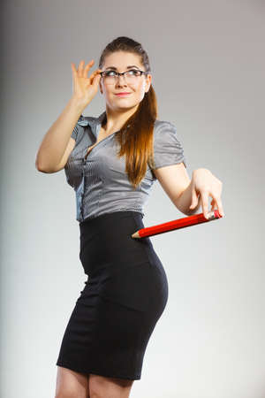 Teacher looking elegant woman wearing dark tight skirt, shirt and eyeglasses holding big oversized pencil Imagens