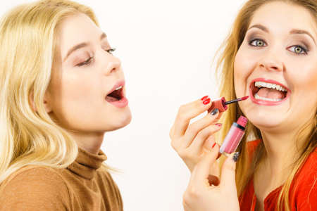 Make up artist friend applying another woman lipstick or lip gloss on lips. Two friends interested in visage.